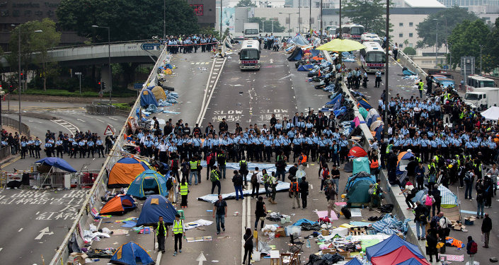 Police officers stand in a line as they prepare to clear tents outside Hong Kong's Government complex in Hong Kong