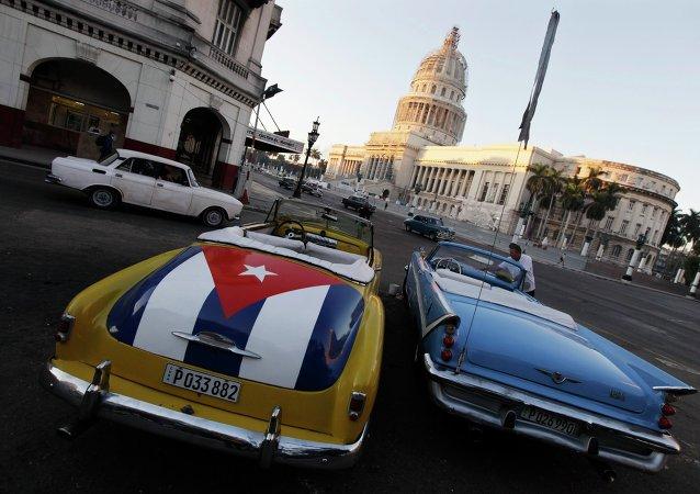 A car with a Cuban flag is parked near Cuban Capitol in Havana