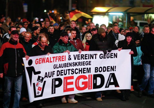 Participants hold a banner during a demonstration called by anti-immigration group PEGIDA, a German abbreviation for Patriotic Europeans against the Islamization of the West, in Dresden December 15, 2014. Several thousands opponents of Germany's policy towards asylum seekers and Islam took part in the protest in the eastern German town on Monday. The banner reads, Peaceful and united against wars of religion in Germany!