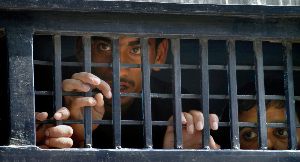 Detained anti-government activists peer out from a prison van after their court appearance in Islamabad, Pakistan