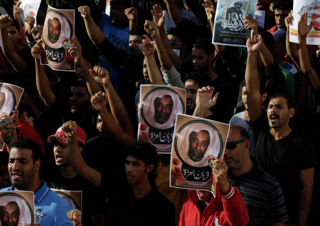 Bahraini anti-government protesters hold up images of Abdul Karim al-Basri and shout slogans during his funeral in Karzakan village, Bahrain, Thursday, Dec. 11, 2014.