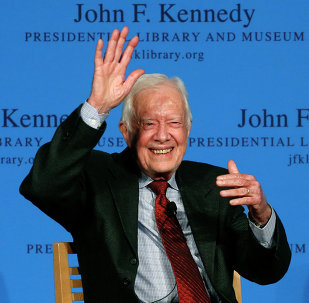 Former President Jimmy Carter waves to a member of the audience after a forum at the John F. Kennedy Presidential Library and Museum in Boston