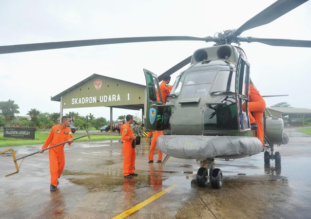 A search and rescue squad from the Indonesian Airforce prepare to depart on a Puma helicopter to take part in the search for the missing AirAsia Flight QZ8501, from a base in Kubu Raya, West Kalimantan