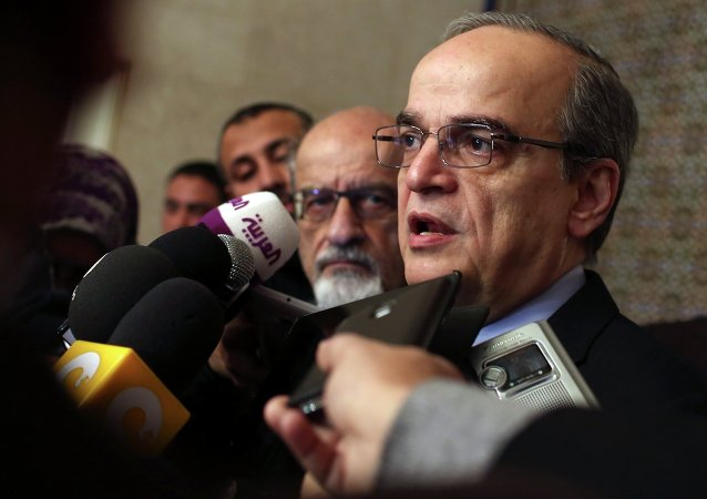 Hadi al-Bahra (R), head of the Syrian National Coalition, and Syrian opposition member Haitham al-Maleh, who is standing next to him, talk to the media