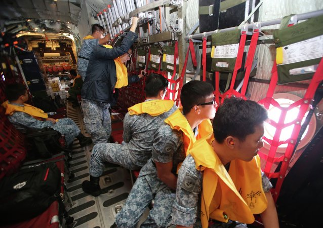 Republic of Singapore Air Force (RSAF) personnel survey the waters onboard a C-130 Hercules during a Search and Locate operation for the missing AirAsia QZ8501 aircraft over an undisclosed search area December 29, 2014