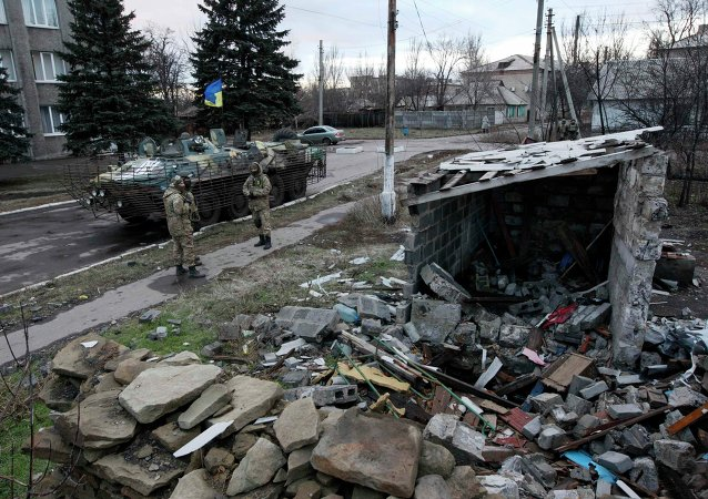 Ukrainian servicemen stand near a building damaged during fighting between militia and Ukrainian government forces in the eastern Ukrainian town of Debaltseve in Donetsk region, December 24, 2014