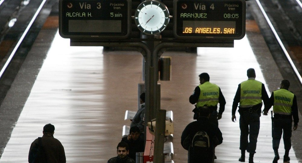 Security guards patrol the platform as passengers wait for a train at Atocha station