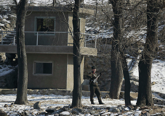 A North Korean soldier stands guard on the river bank of the North Korean town of Sinuiju, opposite the Chinese border