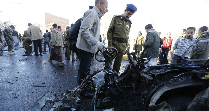 Police investigators look at the wreckage of a car at the scene of a car bomb outside the police college in Sanaa January 7, 2015