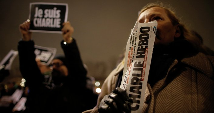 A man holds a copy of weekly satirical magazine Charlie Hebdo to pay tribute during a gathering at the Place de la Republique in Paris, with another holding a sign reading Je suis Charlie - I am Charlie, a statement of solidarity with and mourning for the writers and cartoonists killed in Wednesday's brutal attack