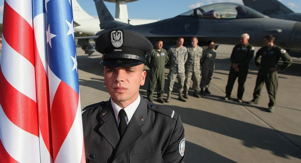 A soldier with the US flag stands on the tarmac during the final preparations before NATO Secretary General Jens Stoltenberg of Norway visits the 32 Tactical Air Base in Lask, Poland, Monday, October 6, 2014.