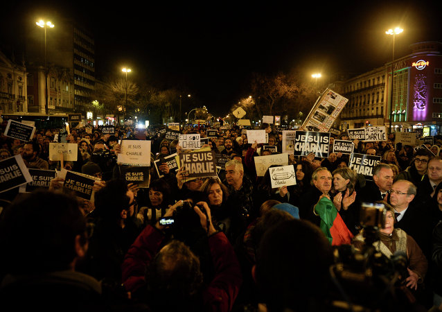 Hundreds of people gather holding pencils and posters reading Je Suis Charlie (I Am Charlie) during a tribute for victims of a terror attack on French satirical weekly Charlie Hebdo in Paris that left 12 dead, at the Restauradores square in Lisbon on January 8, 2015