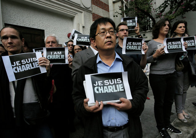 Journalists and supporters of press freedom show off signs reading Je Suis Charlie (I Am Charlie) during a gathering to pay respects for the victims of a terror attack against French newspaper Charlie Hebdo, in Paris, outside The Foreign Correspondents' Club in Hong Kong, Thursday, Jan. 8, 2015