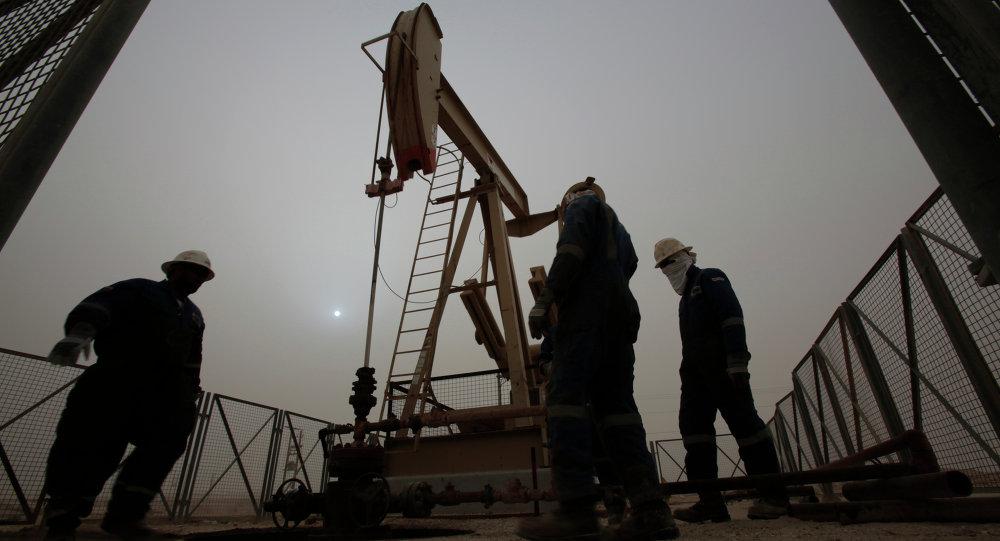 Men work on an oil pump during a sandstorm that blew in Thursday, Jan. 8, 2015, in the desert oil fields of Sakhir, Bahrain
