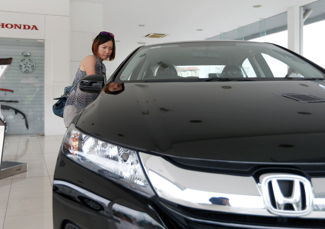 In this Dec. 22, 2014 photo, a woman checks out a new Honda City at a Honda showroom in Petaling Jaya, Malaysia