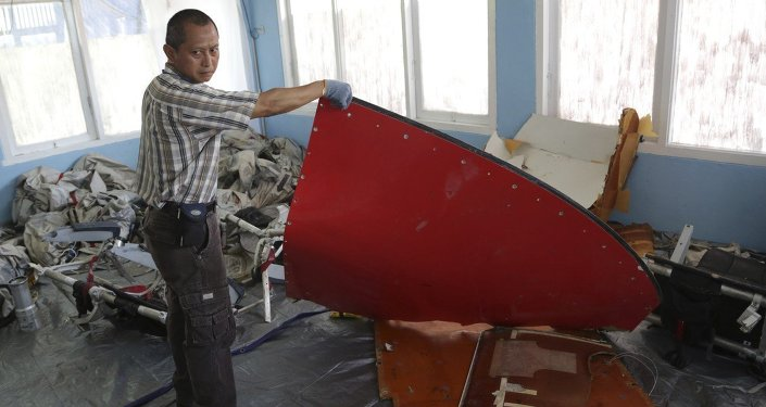 A member of Indonesian Search and Rescue Agency holds a piece which Indonesian Air Force confirmed as from AirAsia Flight 8501, at Disaster Victim Identification room in Pangkalan Bun, Indonesia, Friday, Jan. 9, 2015