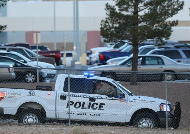 A Fort Bliss Military Police vehicle drives along the perimeter of the El Paso VA parking lot as officers searched for a gunman following a shooting inside the facility Tuesday, Jan. 6, 2014.