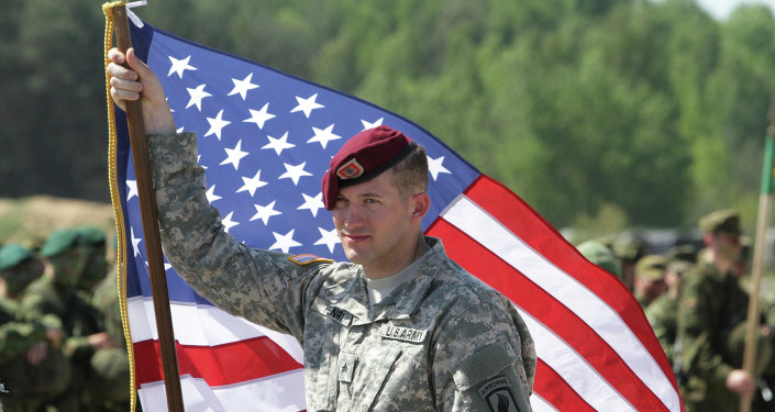 A paratrooper of the 173rd Airborne Brigade of the US Army in Europe holds his country's flag after the final operation of the exercise Black Arrow 2014 in Rukla, Lithuania