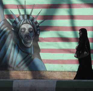 A woman walking past the outer wall of the former US embassy in Tehran, which was seized by Islamists in 1980