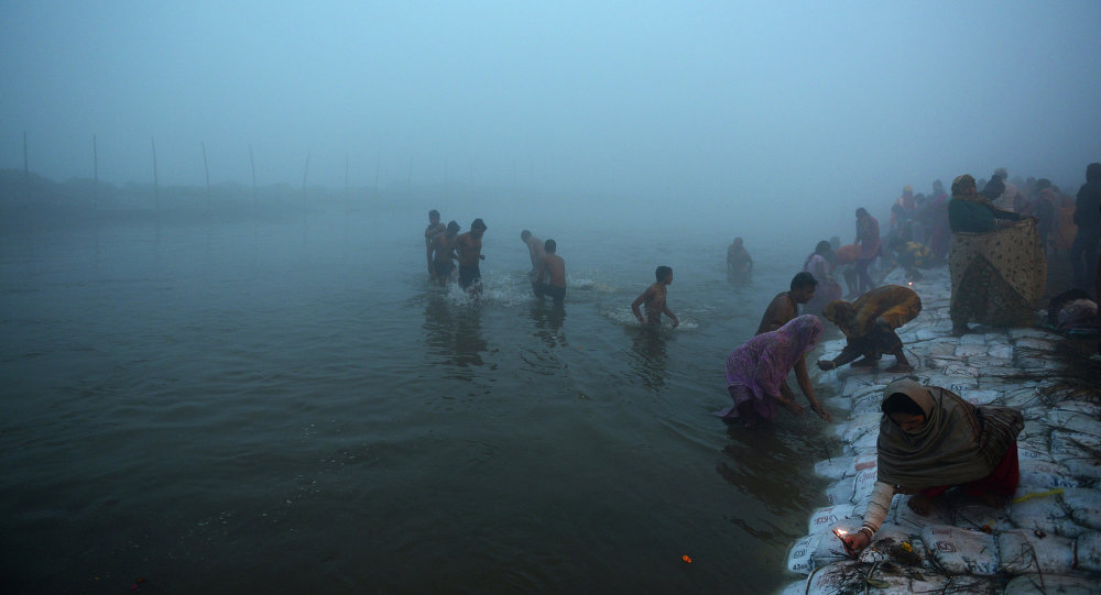 Indian Hindu devotees take a holy dip for the Makar Sankranti festival during the annual Magh Mela gathering at Sangam, the confluence of the rivers Ganges, Yamuna and the mythical Saraswati, during a cold and foggy morning in Allahabad on January 14, 2015