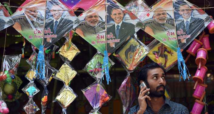 An Indian shopkeeper talks on his mobile phone below kites with images of Indian prime minister Narendra Modi (L) and US President Barack Obama (R) in Mumbai on January 7, 2015