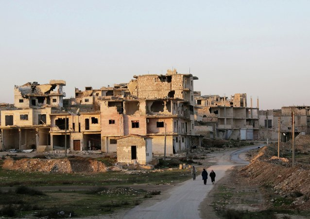 Residents walk near damaged buildings in Maaret al-Naaman town in Idlib province January 14, 2015