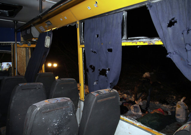 Bodies (R) are laid out next to a damaged bus hit during shelling apparently aimed at a checkpoint manned by Ukrainian forces in Volnovakha, in the eastern Donetsk region