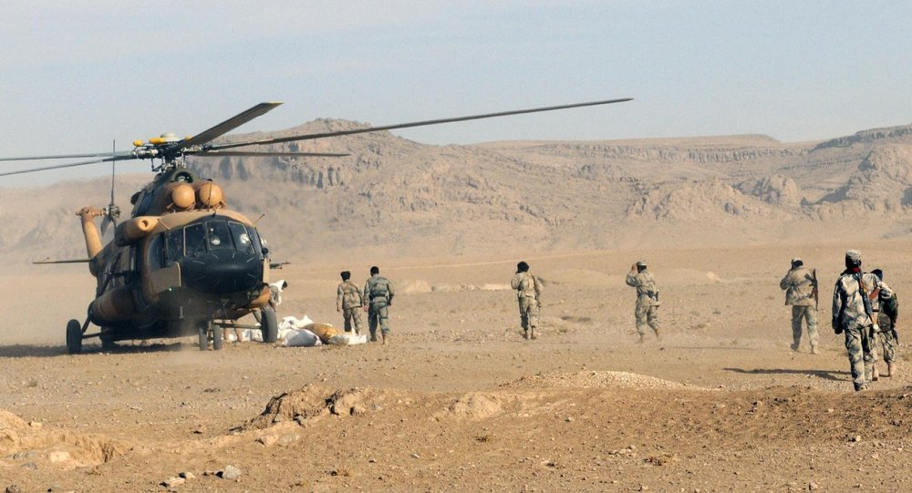 Afghan Border Police members and Kandahar Air Wing pilots offload humanitarian aid from an Afghan Air Force Mi-17 helicopter