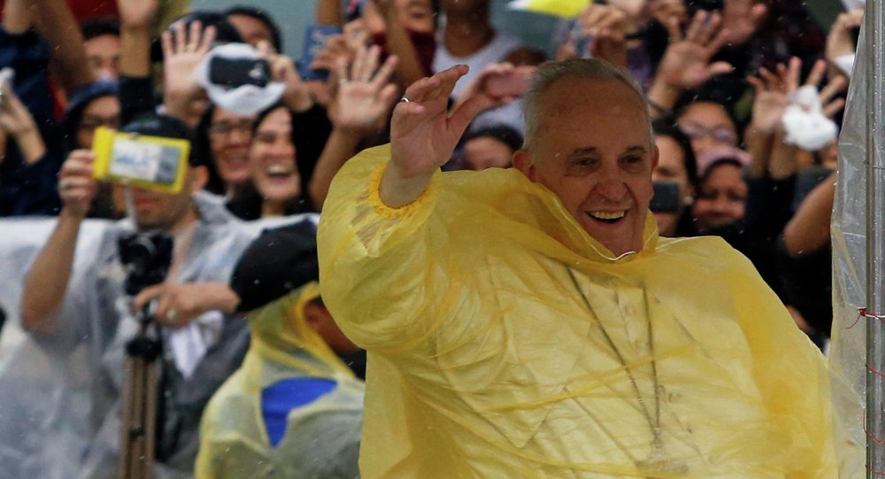 Pope Francis smiles as he waves to residents during a motorcade in Tacloban city, after holding a mass near the airport, January 17, 2015