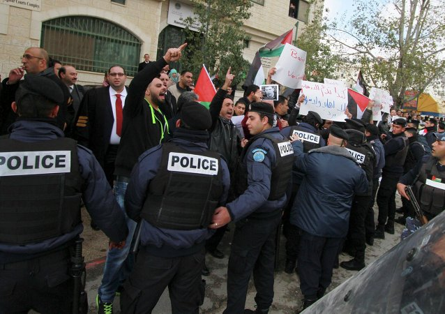 Palestinian policemen hold back demonstrators protesting against Canadian Foreign Minister John Baird, as Baird meets with his Palestinian counterpart in the West Bank city of Ramallah, January 18, 2015.