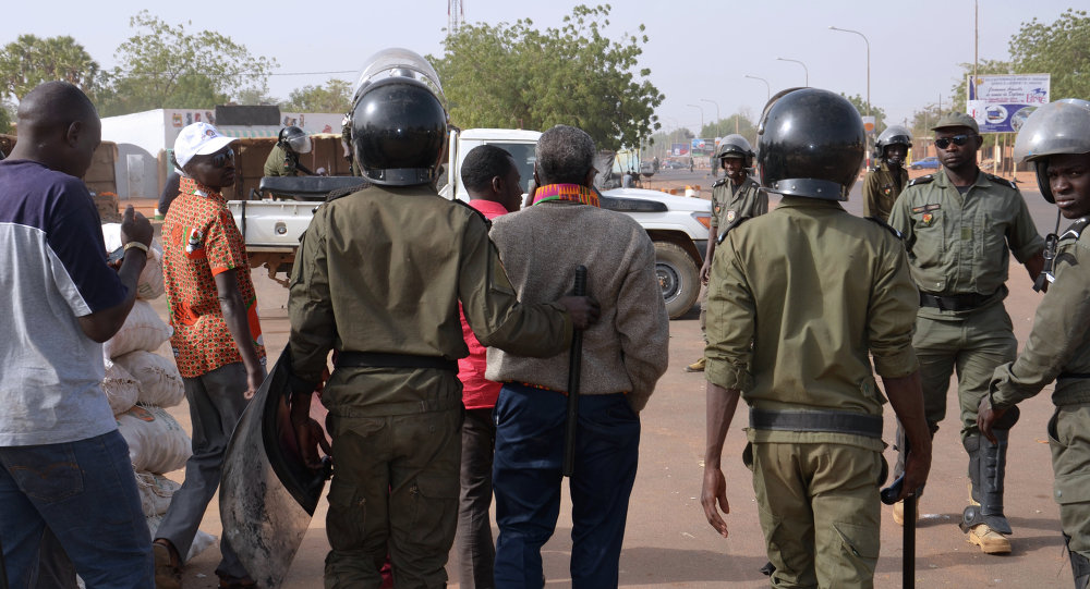 Police officers walk next to protesters as they disperse a banned opposition demonstration in the capital Niamey on January 18, 2015