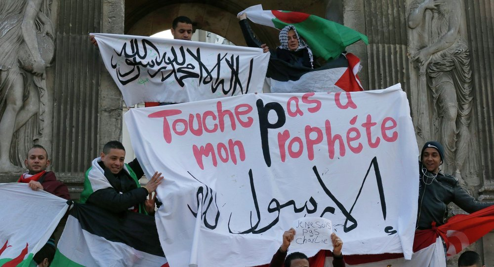 French Muslim youths hold a Islamic flag (top) and a banner reading Do not touch my prophet, anything but the Messenger of Allah as they gather in central Paris January 18, 2015