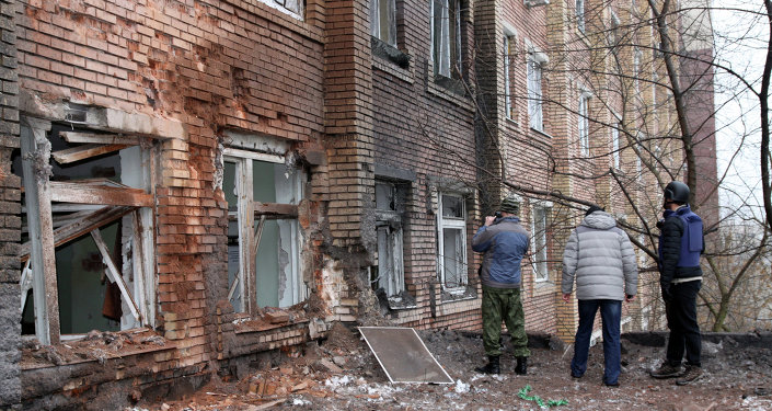 Journalists stand in front of a hospital destroyed after shelling between Ukrainian forces and pro-Russian separatists in the eastern Ukrainian city of Donetsk