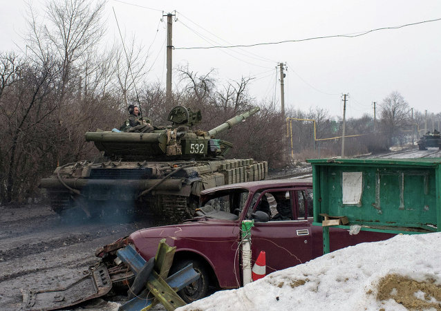 A man rides a Ukrainian tanks past a damaged vehicle in the village of Tonenke, some 5 kilometers from the Donetsk airport