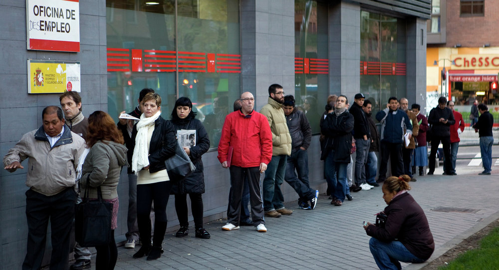 People wait in line at a government employment office on Paseo de las Acacias in Madrid