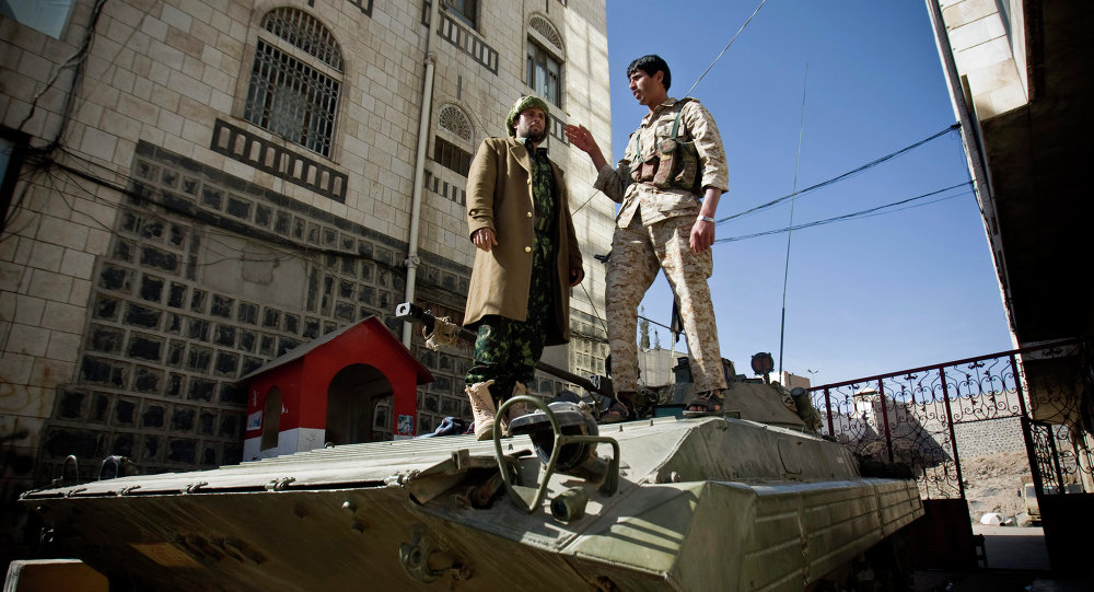 Houthi Shiite Yemeni wearing army uniforms stand atop an armored vehicle, which was seized from the army during recent clashes, outside the house of Yemen's President Abed Rabbo Mansour Hadi in Sanaa, Yemen, Thursday, Jan. 22, 2015