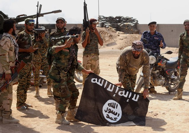 Iraqi security forces hold a flag of the Islamic State group they captured during an operation outside Amirli, some 105 miles (170 kilometers) north of Baghdad, Iraq