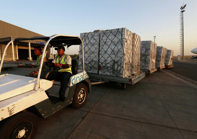 Airport personnel tow 60 tons of humanitarian supplies from USAID