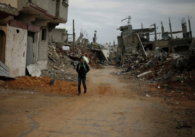 A Palestinian walks near the remains of houses, that witnesses said were destroyed or damaged by Israeli shelling during the July-August war between Israel and Hamas-led Gaza militants, in the east of Gaza City