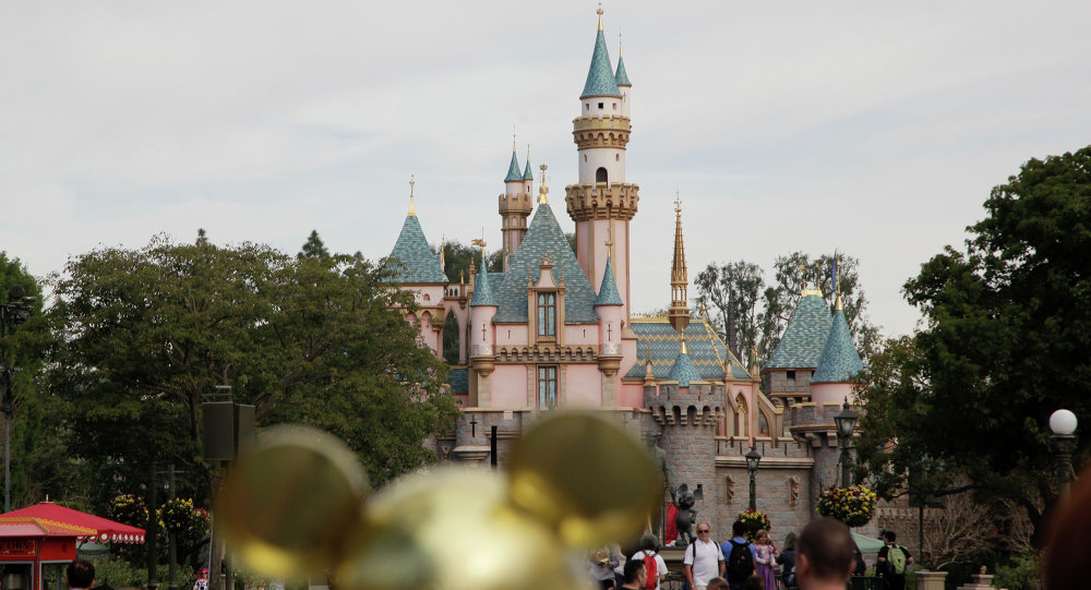 People walk toward the Sleeping Beauty's Castle in the background at Disneyland, Thursday, Jan. 22, 2015, in Anaheim, Calif