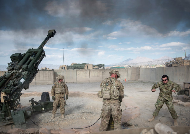 This photo taken on May 28, 2014 shows US Army Sergeant (retired) Joshua Ben, of Missouri (R) who lost his leg to an Rocket Propelled Grenade (RPG) in Afghanistan's Jalrez Valley in 2007, firing artillery during 'Operation Proper Exit' at Forward Operating Base Shank in Afghanistan's Logar Province