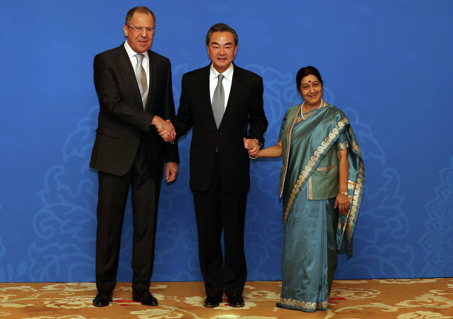 Russian Foreign Minister Sergei Lavrov (L), Chinese Foreign Minister Wang Yi (C) and Indian Foreign Minister Sushma Swaraj (R) shake hands as they for photographs before the thirteenth meeting of the Foreign Ministers of the China, Russia and India in Beijing on February 2, 2015