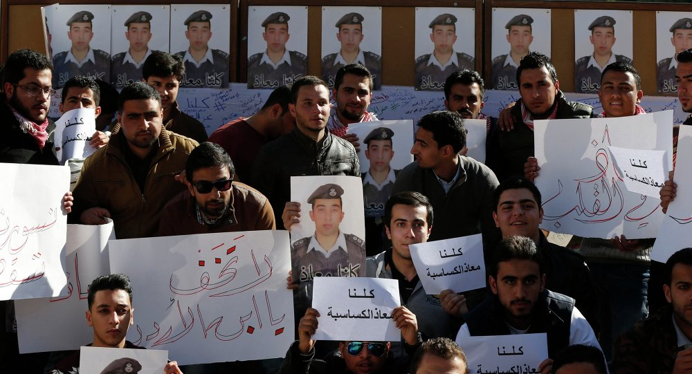 Students hold pictures of Islamic State captive Jordanian pilot Muath al-Kasaesbeh