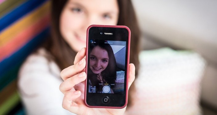 A teenage girl taking a picture of herself on her smartphone