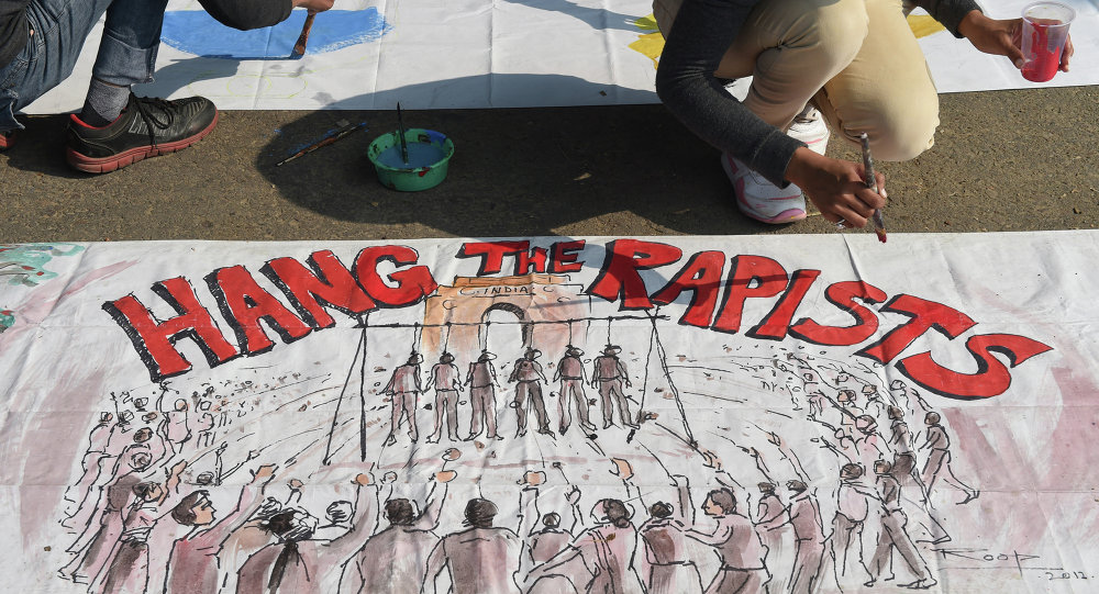 An Indian artist works on a banner condemning rape in New Delhi on December 16, 2014