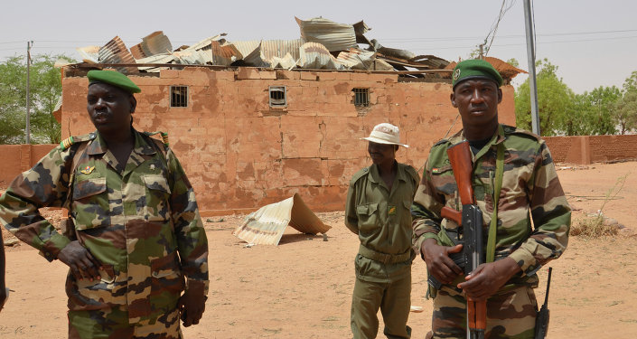 Nigerien soldiers stand near a damaged building in an army base in Agadez, northern Niger on May 26, 2013
