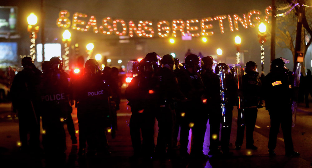 Police in riot gear use tear gas to clear the street in front of the Ferguson Police Department after the announcement of the grand jury decision not to indict police officer Darren Wilson in the fatal shooting of Michael Brown, an unarmed black 18-year-old, Monday, Nov. 24, 2014, in Ferguson, Mo.