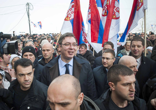 Kosovo Serbs gather holding up their national flag as they welcome Serbian Prime Minister Aleksandar Vucic, surrounded by body guards, to the village of Pasjane, during his visit to Kosovo.