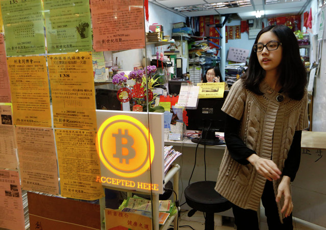 A staff member from a travel agency displays a Bitcoin logo as they accept bitcoins for payment in Hong Kong Friday, Feb. 28, 2014, after the world's first bitcoin retail store opened in Hong Kong, despite the virtual currency facing much scrutiny.