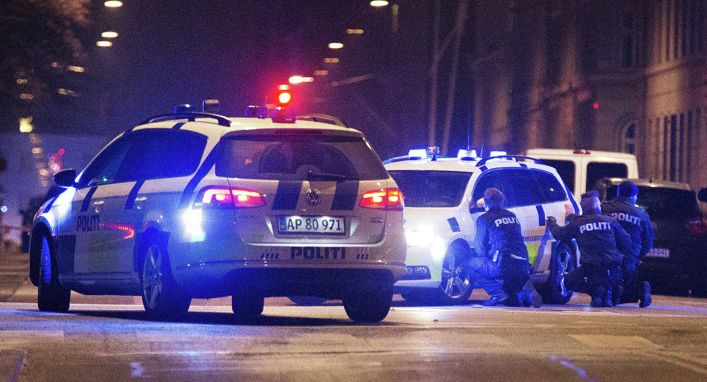 Police officers take cover behind their patrol cars on the streets of central Copenhagen on February 15, 2015